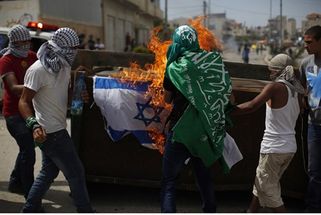 Protesters burn an Israeli flag during clashe